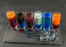 Opinión del lado derecho sobre seis diversas bebidas coloreadas del tiro, alineadas Fotografía de archivo libre de regalías