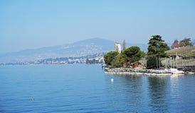 Opinión del lago, fondo del cielo y de la montaña, y paisaje urbano azules de los edificios foto de archivo