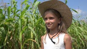 Opinión del niño en el campo de maíz que mira al granjero Girl Smiling Outdoor de los granos en la naturaleza 4K almacen de metraje de vídeo