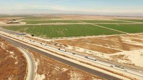 Opinión del ojo de pájaro del tráfico de la autopista sin peaje por las tierras de labrantío agrícolas almacen de metraje de vídeo