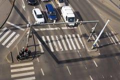 Opinión del ojo del ` s del pájaro de los coches que cruzan la intersección con la gente que camina en paso de peatones el 3 de m Imagenes de archivo