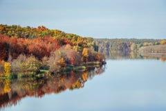 Opinión del otoño de la caída sobre el bosque coloreado multi del otoño que refleja en el río Imagen de archivo libre de regalías