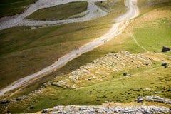 opinión del Pájaro-ojo de una trayectoria de la montaña con los caminantes en ella Imagen de archivo libre de regalías