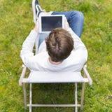 Opinión del pájaro sobre persona irreconocible con la tableta digital que sienta o Imagen de archivo
