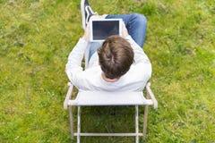 Opinión del pájaro sobre persona irreconocible con la tableta digital que sienta o Imágenes de archivo libres de regalías