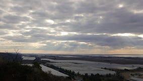 Opinión del paisaje de la tarde sobre la costa costa, el cielo, las nubes, el valle con la reserva de agua y naranjales del mar M Fotos de archivo