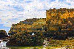 Opinión del paisaje del fondo de un puente arqueado entre las rocas en una de las playas de Lagos Foto de archivo