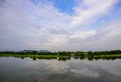 Opinión del panorama del cielo azul y reflexión de la nube en el río Imagenes de archivo