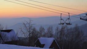 Opinión del panorama sobre puesta del sol en las montañas, la telesilla y las casas de madera en la colina almacen de metraje de vídeo