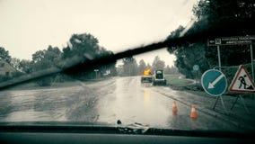 Opinión del parabrisas en las fuertes lluvias que conducen a través de sitio de la construcción de carreteras
