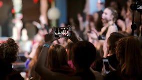 Opinión del primer algunas muchachas que filman en sus smartphones Muchedumbre borrosa, feliz, que anima en el fondo almacen de metraje de vídeo