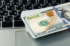 Opinión del primer de cientos billetes de banco del dólar que mienten en el teclado del ordenador portátil imagen de archivo libre de regalías