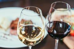 opinión del primer de dos vidrios con el vino blanco rojo y en la tabla en restaurante Fotografía de archivo libre de regalías