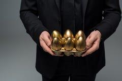 Opinión del primer de huevos de oro en manos del varón foto de archivo libre de regalías