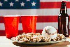 opinión del primer de la bola del béisbol en la placa con los cacahuetes, las tazas plásticas rojas y la botella de cerveza imagenes de archivo