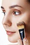 Opinión del primer de la cara de la muchacha de la belleza con los cepillos del maquillaje travieso Fotos de archivo