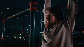Opinión del primer de la cara tensada del hombre joven que entrena al aire libre en noche metrajes