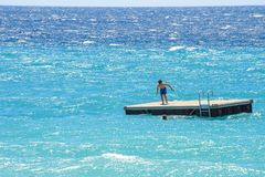 Opinión del primer de la luz del día al hombre que se prepara para saltar en el w azul Foto de archivo