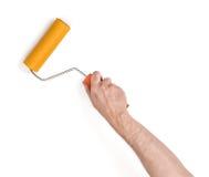 Opinión del primer de la mano del hombre con el rodillo de pintura, aislada en el fondo blanco Imagen de archivo