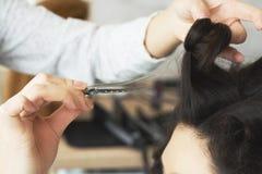 Opinión del primer de la mano del peluquero que peina un nuevo peinado en una cabeza del cliente en salón de pelo foto de archivo libre de regalías