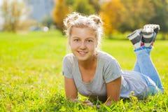 Opinión del primer de la muchacha que pone en hierba verde Imagen de archivo libre de regalías