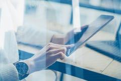 Opinión del primer de la tableta digital de la exhibición conmovedora femenina de la mano en la tabla de madera El usar del conce fotos de archivo