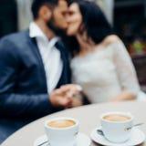 Opinión del primer de las dos tazas de café en el fondo borroso de los recienes casados que se besan Fotografía de archivo libre de regalías