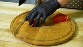 Opinión del primer de las manos del cocinero en los guantes que cortan el tomate en tabla de cortar de madera redonda almacen de metraje de vídeo