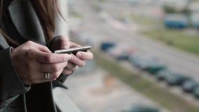 Opinión del primer de las manos femeninas que sostienen el smartphone, mujer joven que hojea Internet afuera del teléfono móvil metrajes