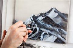 Opinión del primer de las manos humanas que dibujan con el aerógrafo en lona, pintando con el aerógrafo Fotografía de archivo libre de regalías