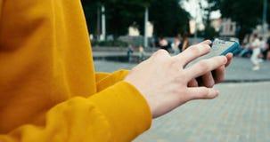 Opinión del primer de las manos masculinas el desconocido en el suéter amarillo que manda un SMS y que hojea en el teléfono móvil metrajes