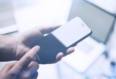 Opinión del primer de las manos masculinas que sostienen smartphone moderno y que señalan el finger al botón casero Fondo horizon Imágenes de archivo libres de regalías
