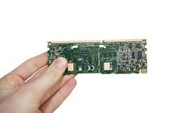 Opinión del primer de las manos que llevan a cabo la placa de circuito del ordenador sobre el fondo blanco Foto de archivo libre de regalías