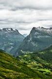 Opinión del primer de las montañas en Noruega occidental con los pequeños pueblos y ciudad en la parte inferior del valle y de la Fotografía de archivo