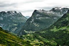 Opinión del primer de las montañas en Noruega occidental con los pequeños pueblos y ciudad en la parte inferior del valle y de la Fotografía de archivo libre de regalías