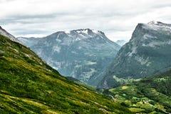 Opinión del primer de las montañas en Noruega occidental con los pequeños pueblos y ciudad en la parte inferior del valle y de la Imágenes de archivo libres de regalías