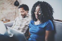 Opinión del primer de los pares afroamericanos felices que se relajan junto en el sofá Hombre negro joven y su usar de la novia Fotografía de archivo
