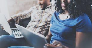Opinión del primer de los pares afroamericanos felices que se relajan junto en el sofá Hombre negro joven y su usar de la novia Fotos de archivo