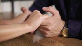 Opinión del primer de los pares jovenes que llevan a cabo las manos que se sientan en la tabla de madera Fecha romántica de pares almacen de video