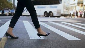 Opinión del primer de los zapatos que llevan de la empresaria joven con los talones que cruzan el camino en centro de la ciudad o almacen de video
