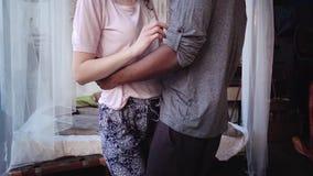 Opinión del primer de pares multirraciales en los pijamas que bailan descalzo Abrazos cariñosos del hombre y de la mujer, tiempo  metrajes