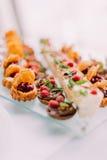 Opinión del primer de pequeños pedazos de dessets adornados con la fruta y el chocolate Imagen de archivo libre de regalías