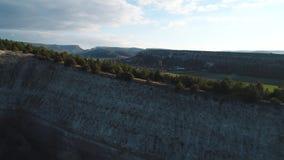 Opinión del primer de un acantilado grande de la montaña con el pequeño pueblo en el fondo contra el cielo azul Fooage Hermoso almacen de video