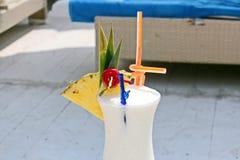 Opinión del primer de un vidrio frío de batido de leche adornado con las frutas tropicales y de un vidrio de vino con un limón de imagen de archivo