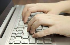 Opinión del primer de una mano con los fingeres que mecanografían en un ordenador portátil de la plata del teclado que miente en  Foto de archivo libre de regalías