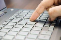 Opinión del primer de una mano con una prensa del finger la llave de entrada en el ordenador portátil de plata del teclado que mi Fotos de archivo