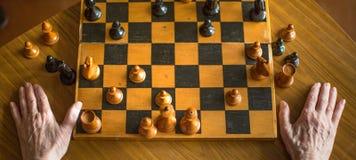 Opinión del primer de una mano de la mujer mayor que juega a ajedrez foto de archivo