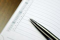 Opinión del primer de una pluma del metal que miente en el diario con un calendario Foto de archivo libre de regalías