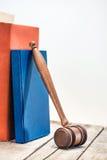 Opinión del primer del mazo de madera del juez y de libros en la tabla de madera foto de archivo