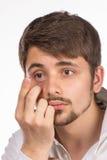 Opinión del primer del ojo marrón de un hombre mientras que inserta una c correctiva fotos de archivo